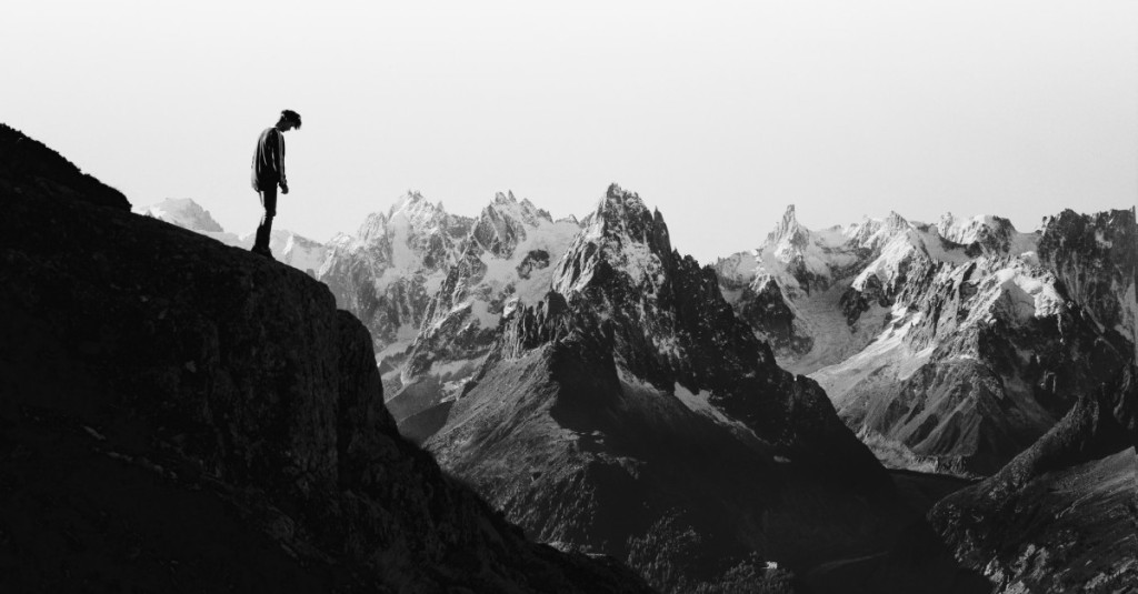 Man standing at the edge of a steep cliff and looking down as if ready to jump